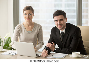 Smiling businessman and businesswoman looking at camera, busines