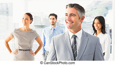 Smiling businessman and his co-workers standing behind