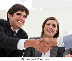 Smiling businessman and his colleague closing a deal with a ...