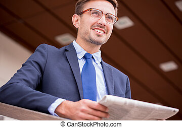Smiling businessman and newspaper