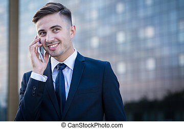 Smiling businessman and phone