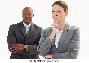Smiling businessman behind businesswoman rests head on hand