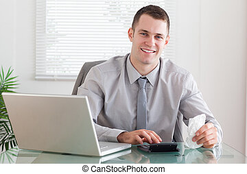 Smiling businessman checking an invoice