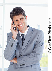 Smiling businessman crossing his arms while making a call