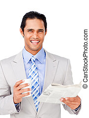 Smiling businessman driking coffee and reading a newspaper