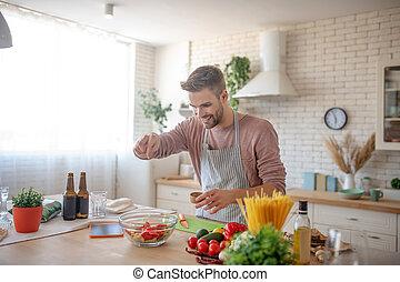 Smiling businessman enjoying weekend cooking at home