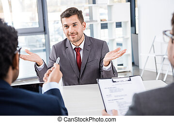 smiling businessman gesturing during job interview, business concept