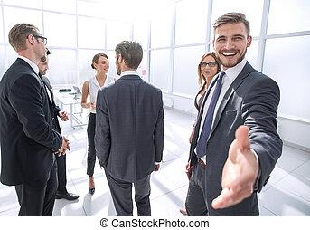 smiling businessman gives hand for handshake