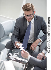 smiling businessman helping the partner to complete the puzzle