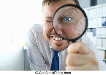 Smiling businessman hold magnifying glass