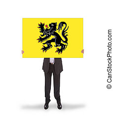 Smiling businessman holding a big card, flag of Flanders