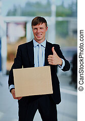 Smiling businessman holding a cardboard box.