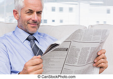 Smiling businessman holding a newspaper