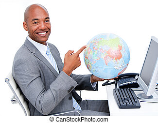 Smiling businessman holding a terrestrial globe in the office