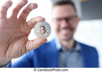 Smiling businessman holding bitcoin. Making money on bitcoins without investments