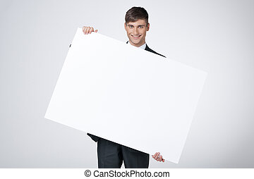 Smiling businessman holding blank poster. Standing isolated on grey