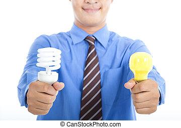 smiling businessman holding energy saving light bulb and tradition light bulb
