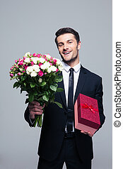 Smiling businessman holding flowers and gift box over gray...
