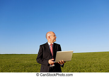 Smiling Businessman Holding Laptop On Field