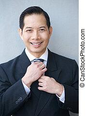 Smiling businessman holding necktie