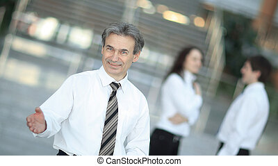 smiling businessman holding out his hand for greeting