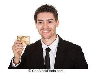 Smiling businessman holding up a credit card