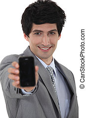 Smiling businessman holding up his mobile phone