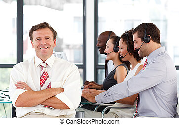 Smiling senior business man standing in a call center