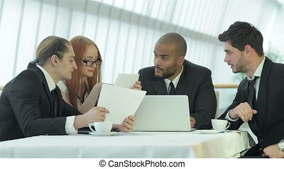 Four smiling successful businessmen sitting at table in office