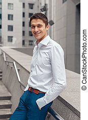 Smiling businessman in formal wear standing outdoors
