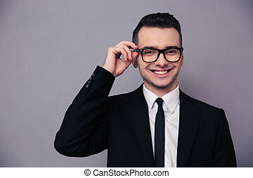 Smiling businessman in glasses looking at camera