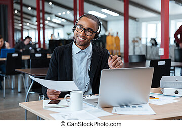 Smiling businessman in headphones holding documents