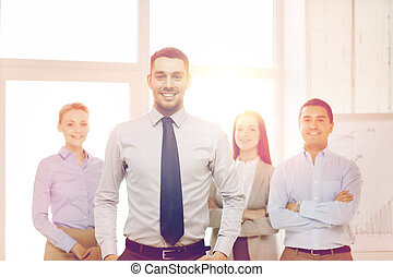 smiling businessman in office with team on back