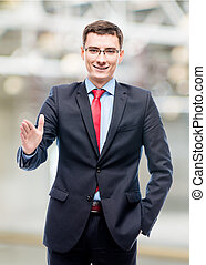 Smiling businessman in suit giving hand in office