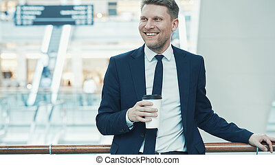 Smiling businessman in suit with coffee