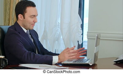 Smiling businessman in the office on video conference