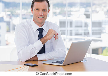 Smiling businessman leaning on his desk