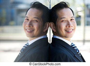 Smiling businessman leaning on wall