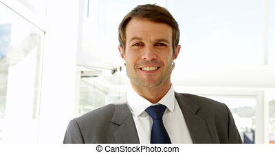Smiling businessman looking at camera in his office