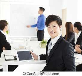 Smiling businessman looking at camera with  colleague