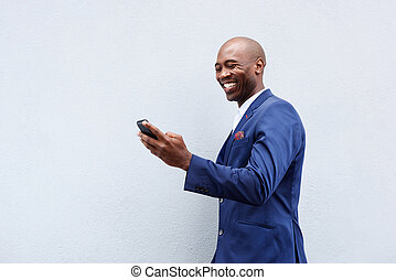 Smiling businessman looking at cellphone