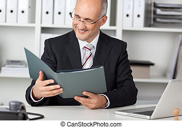 smiling businessman looking at cv