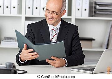 smiling businessman looking at cv