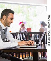 Smiling businessman looking at laptop screen