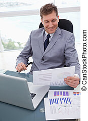 Smiling businessman looking at market research results