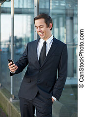 Smiling businessman looking at mobile phone outdoors