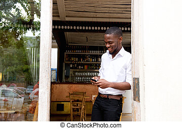 Smiling businessman looking at mobile phone