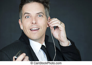Smiling Businessman Looks To Camera As He Puts On Headphones