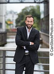 Smiling businessman on a metal bridge