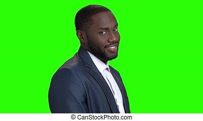 Smiling businessman on chroma key background. Distrustful...